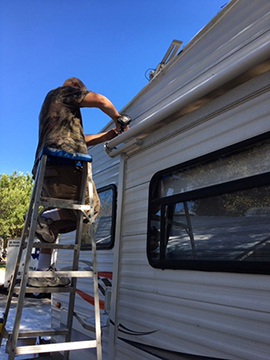 Ron Baker of RVs of Texas working on Slideout room awning